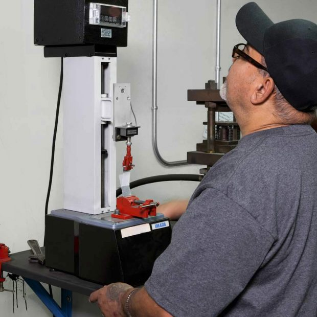 Arvinyl's Quality Inspector uses tensometer tensile testing machine to measure bond strength.